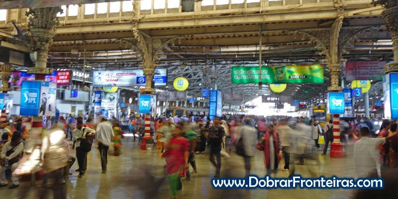 Passageiros no interior da antiga estação de comboio Victoria em Bombaim