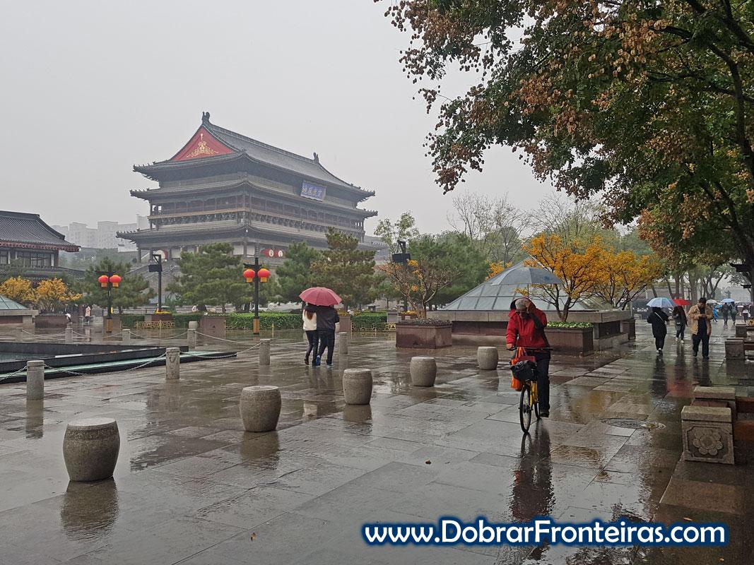 Homem de bicicleta à chuva junto à torre do tambor em Xian, China