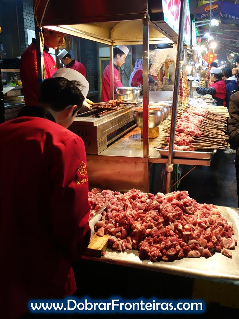 Rapaz preparar carne para as espetadas nas ruas de Xi'an, China